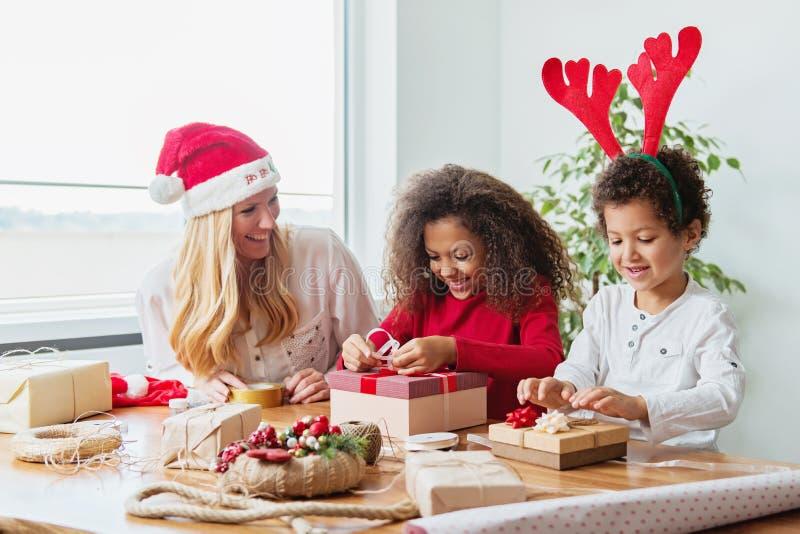 包裹圣诞节礼物的家庭在桌上 免版税库存图片
