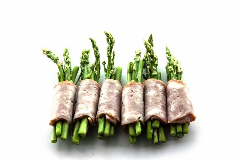包裹在孤立的烟肉芦笋 库存图片