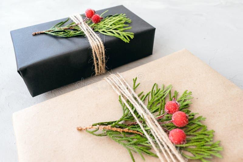 包裹在被回收的纸的圣诞礼物在土气样式 Xmas有工艺纸的礼物盒 免版税库存照片