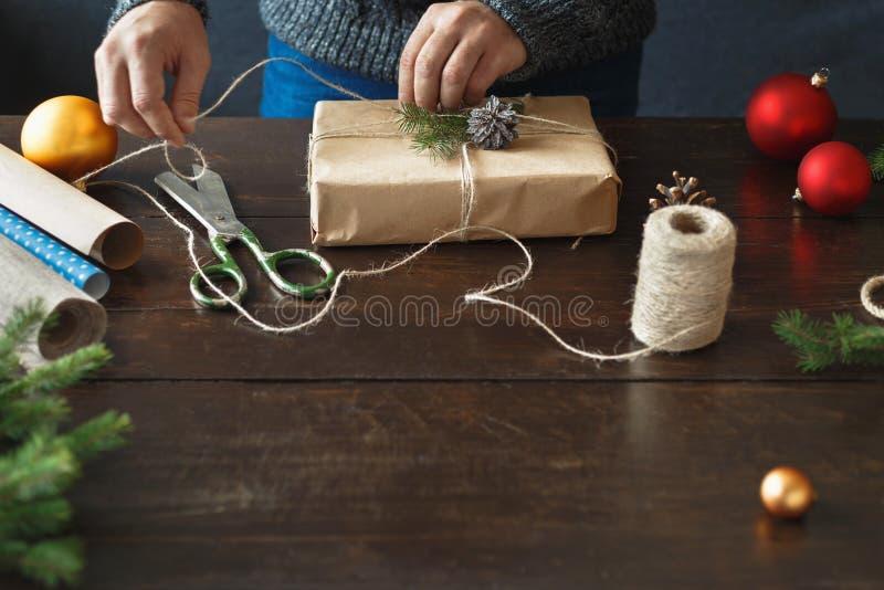 包裹礼物盒木桌土气圣诞礼物背景的男性手 库存图片