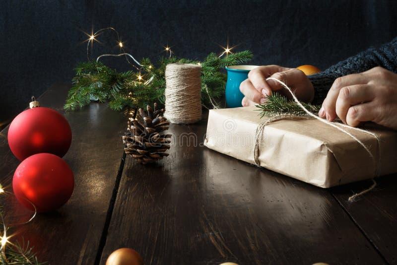 包裹礼物盒木桌土气圣诞节背景的男性手提出背景 免版税图库摄影