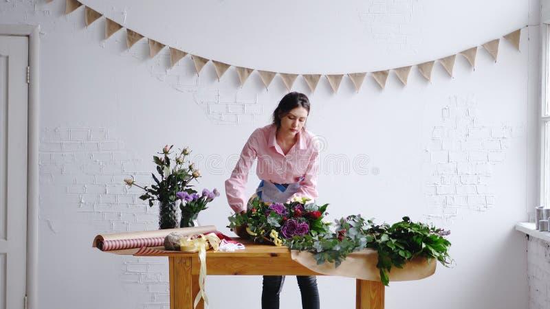 包裹花的大和现代花束在纸的卖花人在花店 图库摄影