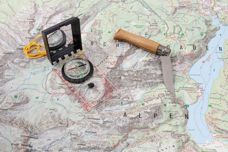 包围并且木处理了在一张远足的地图的刀子 免版税库存照片