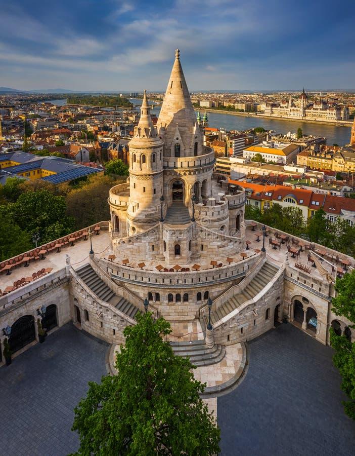 匈牙利布达佩斯 — 日落时空俯瞰著名的渔人堡垒,议会大楼背景 库存图片