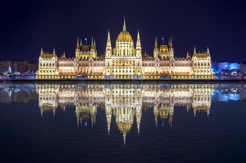 匈牙利议会大厦在与反射的晚上在多瑙河,布达佩斯,匈牙利 库存照片