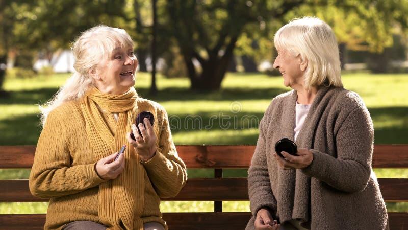 化妆嘴唇和互相看,时尚为长辈的滑稽的成熟妇女 图库摄影