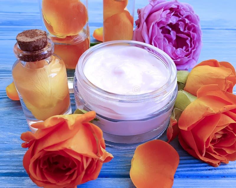 化妆奶油,上升了在木背景的花 免版税库存照片