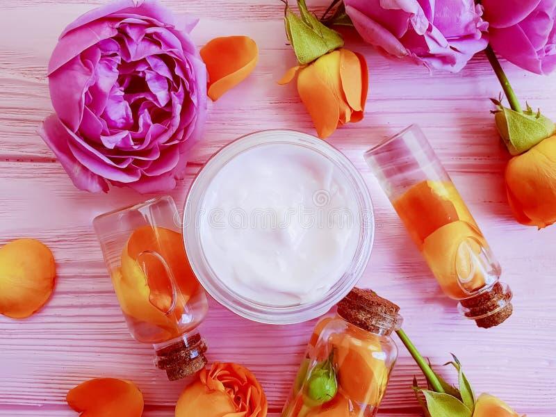化妆奶油,上升了花润湿美好在木背景 免版税库存图片