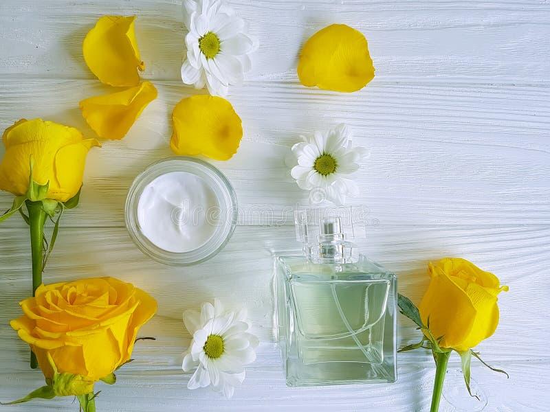 化妆奶油,香水,花黄色在木背景上升了 免版税库存照片