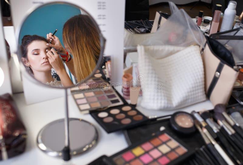 化妆师做补偿女孩 免版税图库摄影