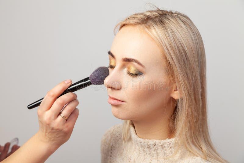 化妆师在与闭上的眼睛的一个白肤金发的模型在她的手上投入构成,躺在了在东方人styleholds的阴影一把刷子 库存照片