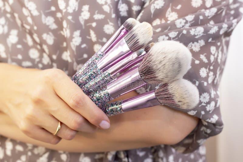 化妆师在女孩模型投入构成 拿着套构成刷子 库存图片