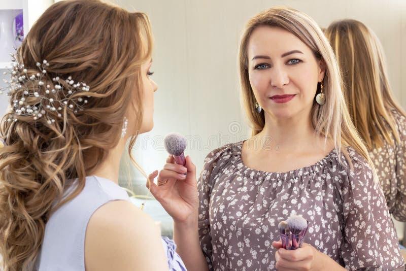 化妆师在女孩模型投入构成 掠过在颧骨和面孔的粉末 美女模型,画象 在makeu的裸体颜色 库存照片