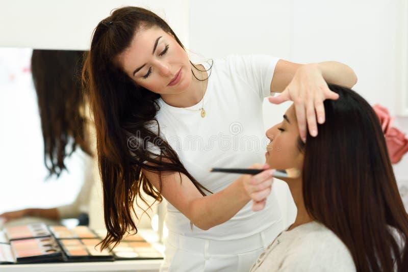 化妆师在秀丽中心的组成非洲年轻女人 免版税图库摄影