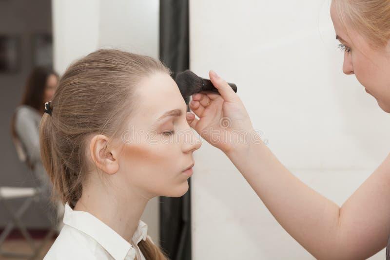 化妆师在photoshoot前应用构成女孩 免版税库存图片