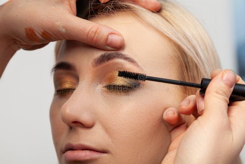 化妆师投入与金子的东方式构成,并且一个年轻可爱的白肤金发的女孩的绿色树荫,绘她的睫毛 免版税库存图片