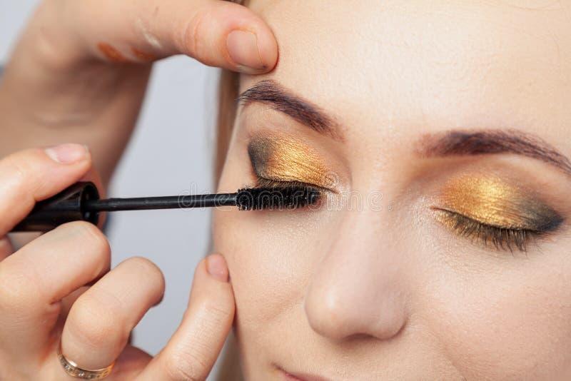 化妆师投入与金子的东方式构成,并且一个年轻可爱的白肤金发的女孩的绿色树荫,绘她的睫毛 库存图片