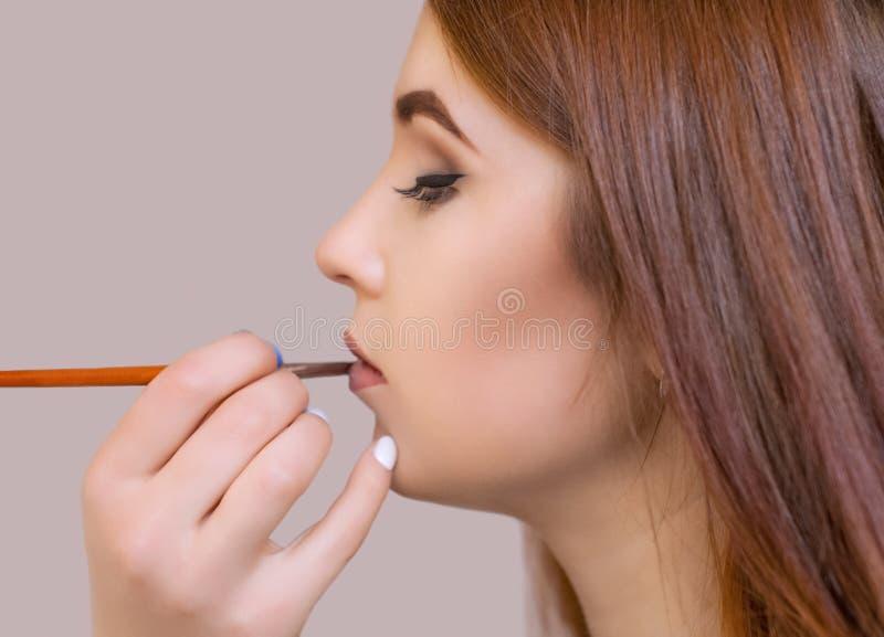 化妆师申请构成并且上色有professiona的唇膏 免版税库存图片
