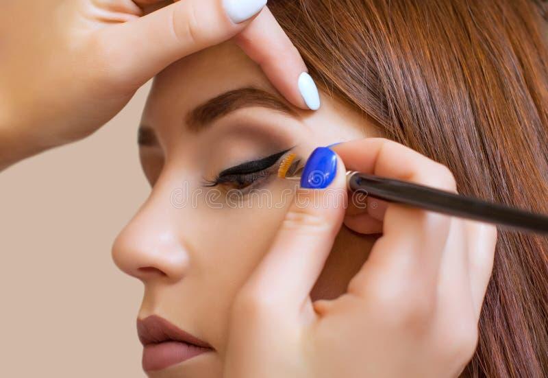 化妆师申请构成并且做与一把专业刷子的眼睛划线员在美容院 免版税库存图片