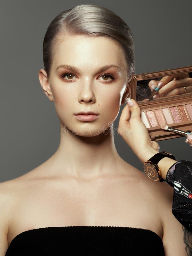 化妆师的人工有刷子的和唇膏围拢的美女在她的面孔附近 愉快的妇女照片  免版税图库摄影