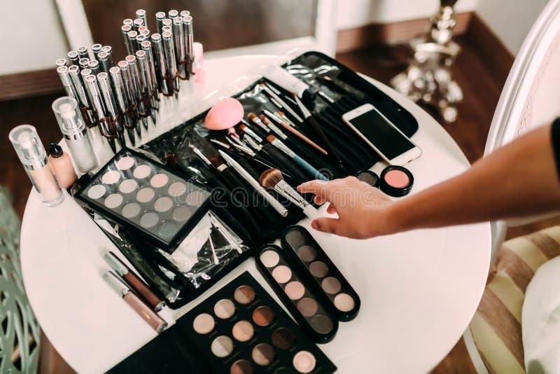 化妆师的手许多化妆用品和刷子在一张桌上在沙龙 工作场所化妆师 库存图片