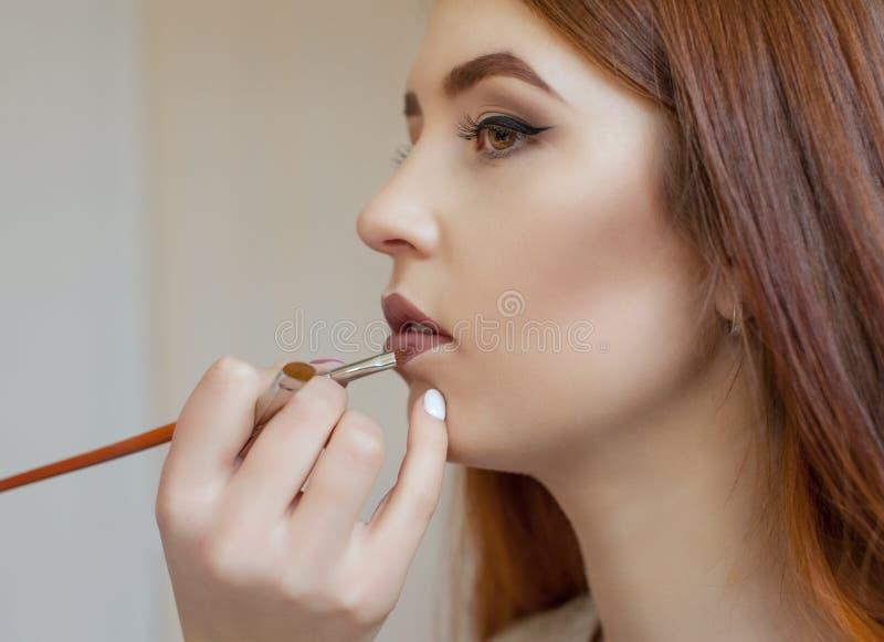化妆师绘一个女孩的嘴唇有唇膏的在美容院 库存图片