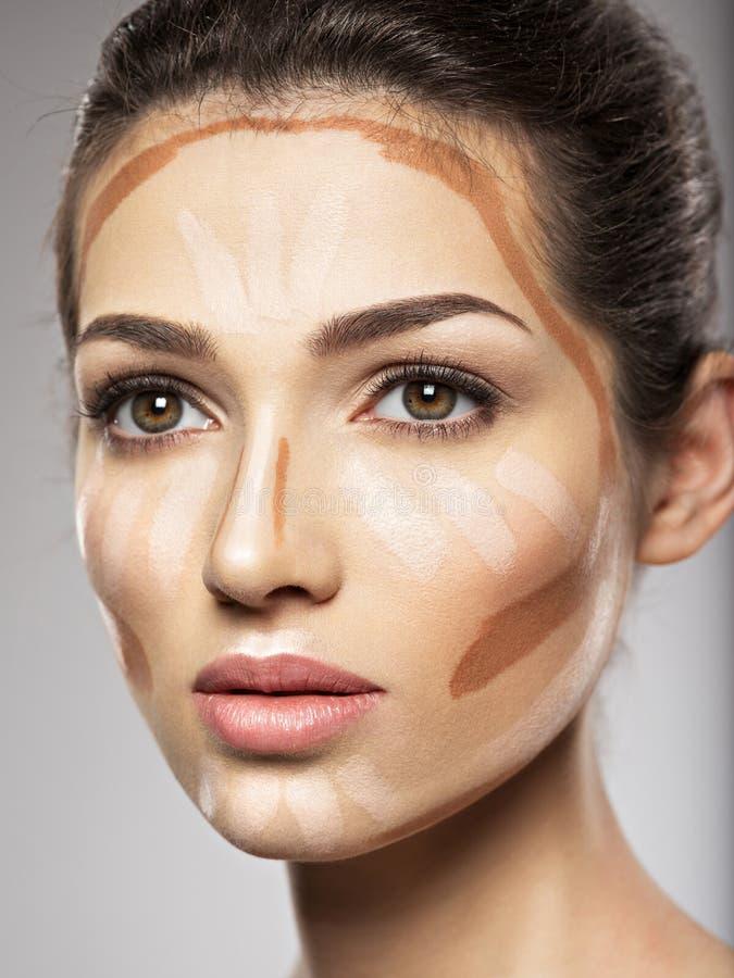 化妆构成音调的基础在妇女` s面孔 免版税库存照片