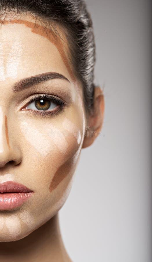 化妆构成音调的基础在妇女` s面孔 库存照片