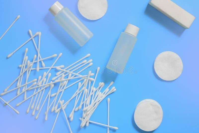 化妆瓶、耳朵棍子和棉花棒在蓝色紫罗兰色背景 r 免版税库存图片