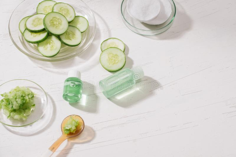 化妆瓶和新鲜的有机黄瓜skincare的 概念重点家有选择性的温泉 免版税库存图片