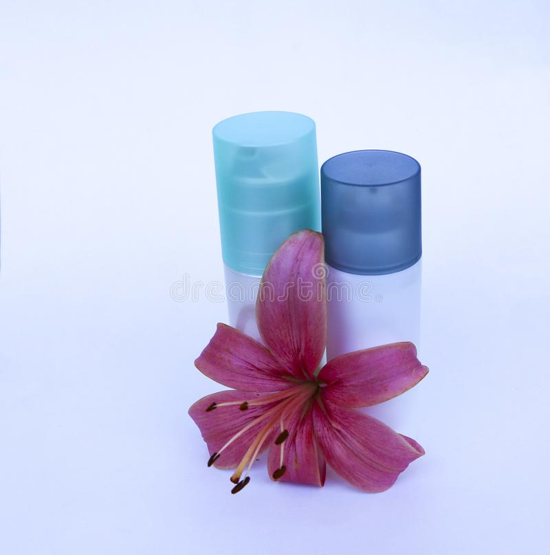 化妆用品为在白色背景的护肤设置了与花百合 润湿的奶油和皮肤洗刷与一个柔和的桃红色百合f 库存图片