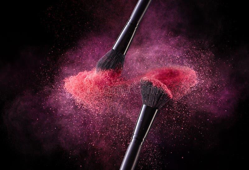 化妆用品刷子和爆炸五颜六色的粉末 免版税库存图片
