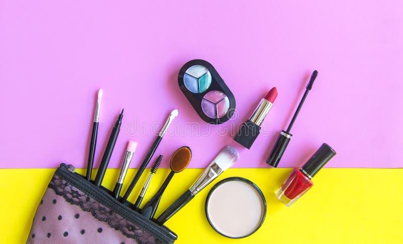 化妆用品和时尚背景与组成艺术家对象:唇膏,眼影,染睫毛油,眼线膏, concealer,指甲油 免版税图库摄影