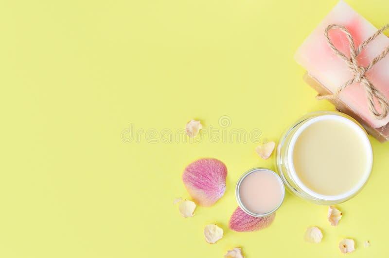 化妆用品提取乳脂,在黄色背景的嘴唇balt 温泉秀丽关心 文本的空间 r 温泉平的位置 桃红色,蓝色 ?? 免版税库存图片