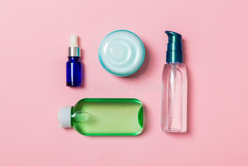 化妆用品温泉烙记的大模型,与拷贝空间的顶视图 套管和瓶子在桃红色背景的奶油色舱内甲板位置 库存照片