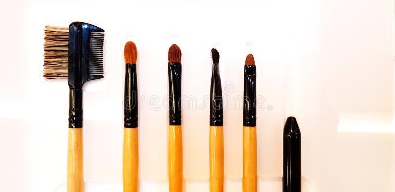 化妆用品的关闭在白色塑料板材组成电刷组在美容院 免版税库存照片