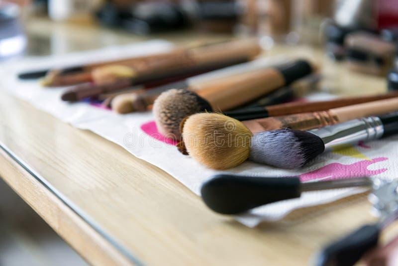 化妆用品的许多刷子在桌上 免版税库存图片