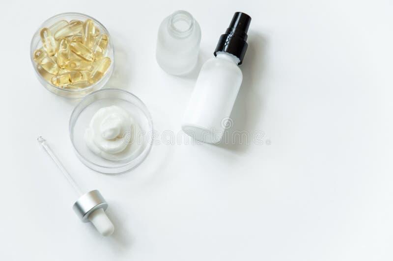化妆用品,成份的创作 在奶油,乳化液,青年时期不老长寿药的维生素  细颈瓶,有吸移管分配器的瓶子 库存图片