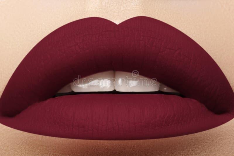 化妆用品,构成 在嘴唇的明亮的唇膏 美丽的女性嘴特写镜头与深红嘴唇构成的 一部分的表面 免版税库存图片