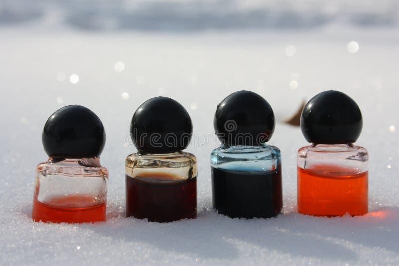 化妆用品 在雪的五颜六色的容器 免版税库存图片