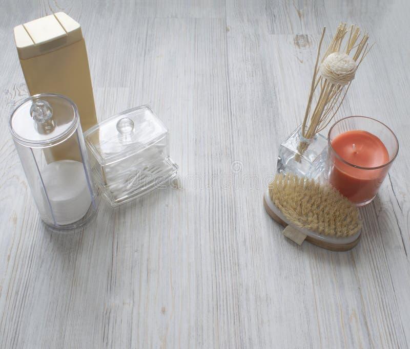 化妆用品flatlay在灰色木桌上 秀丽套塑胶容器、组织者、瓶和蜡烛 r 免版税库存照片