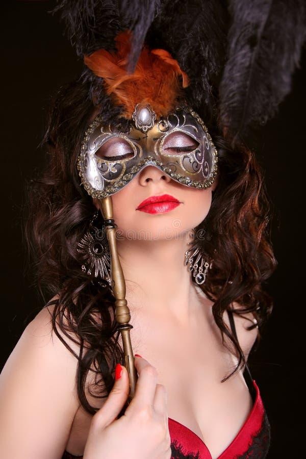 化妆舞会。 有狂欢节面具的性感的妇女在面孔 库存照片