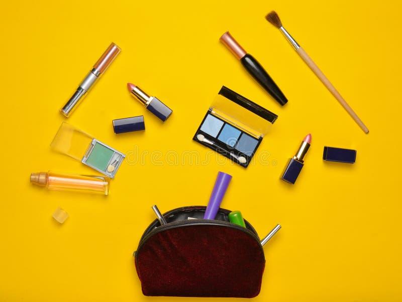 化妆袋子和women' 构成布局的s化妆用品在黄色背景 化妆阴影,构成刷子 免版税库存图片