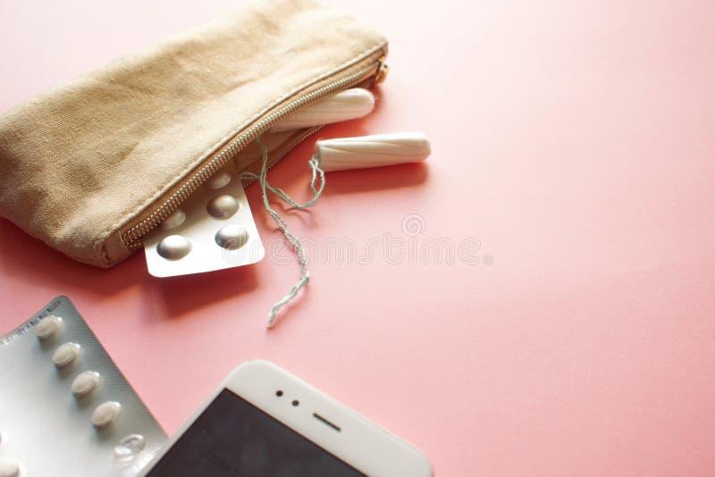 化妆袋子或提包有棉塞、避孕和止痛药片的 设置在月经的情况下 免版税库存图片