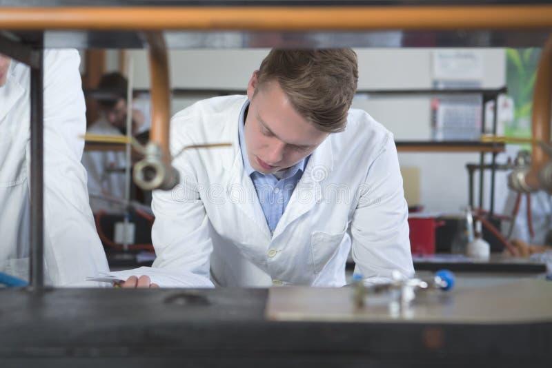 化学、药房和生化的男学生 年轻科学家研究员审查的实验 白肤金发的男性斯堪的纳维亚年轻人 免版税图库摄影