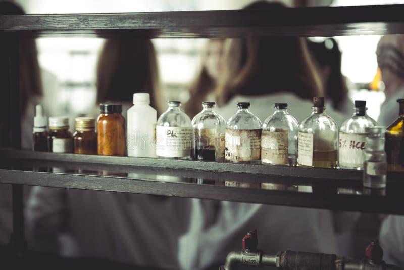 化学制品和实验室器物 葡萄酒在木板的药房瓶 化工瓶为在化学班的使用 安全化工 免版税库存图片