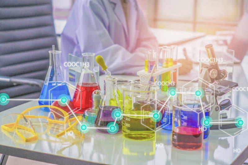 化学家在早晨工作实验室,当太阳发光通过,当制取试样的金属块与五颜六色的液体化学制品一起使用,玻璃管,和 免版税库存图片