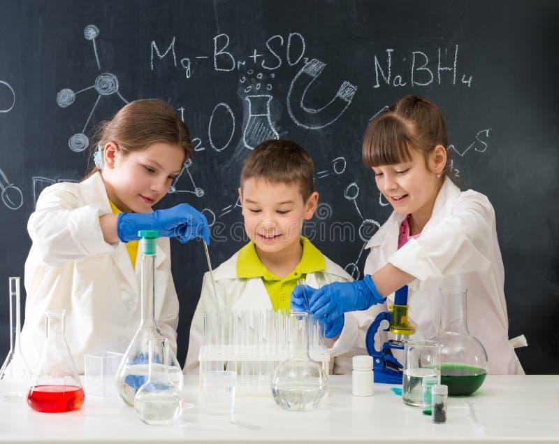 化学教训的三名小学生在实验室 免版税库存图片