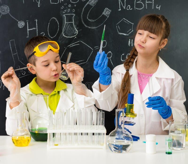 化学教训的两名小学生在实验室 库存照片