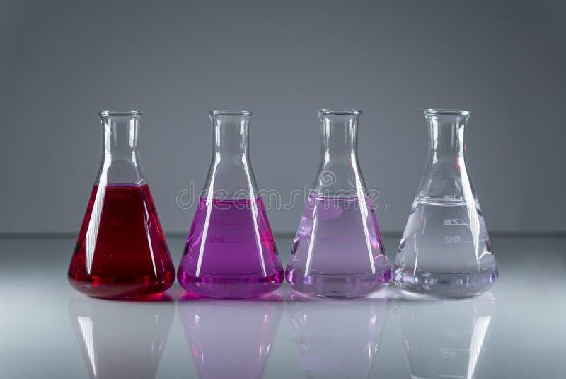 化学烧瓶连续有在他们的另外色的危险毒性液体的 免版税库存照片